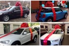 Украшение автомобиля в подарок большим красным бантом.